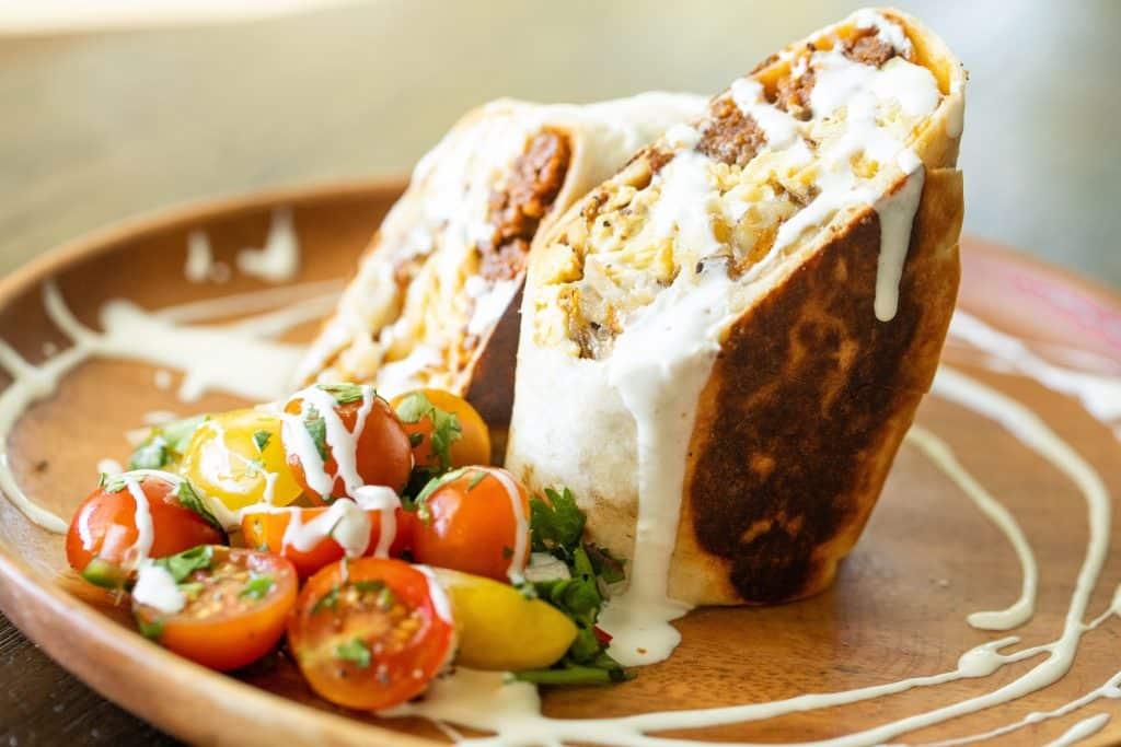halved breakfast burrito on a plate with a side of pico de gallo.