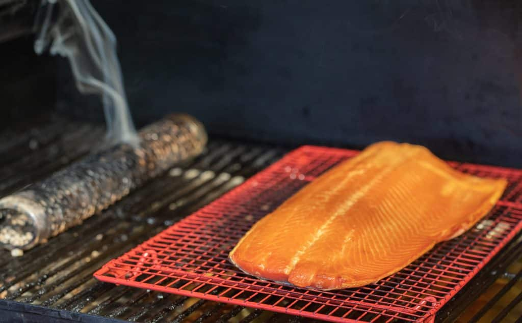 Smoked salmon filet on a cooling rack in a smoker with a steel tube producing wood smoke.