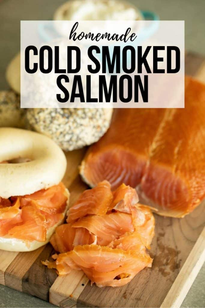 smoked salmon filet and slices on a cutting board with bagels and cream cheese.