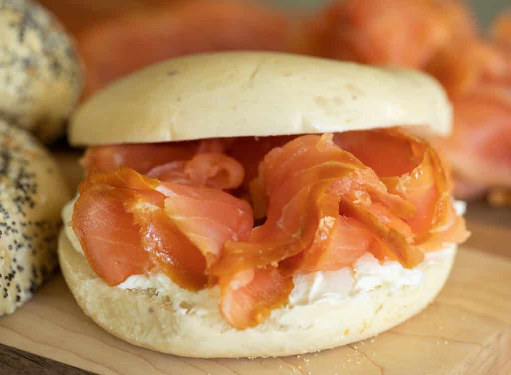 thin sliced smoked salmon piled onto a sliced bagel with cream cheese.