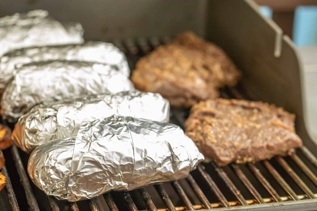 foil-wrapped baked potatoes on the grill