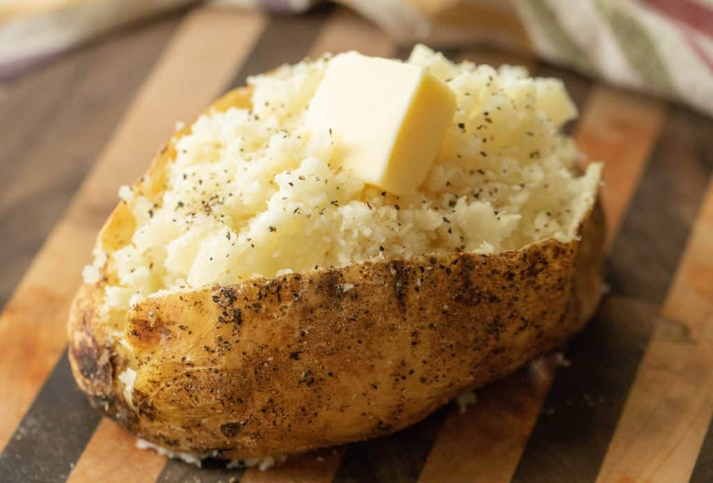 cube of butter on an open baked potato on a wooden cutting board