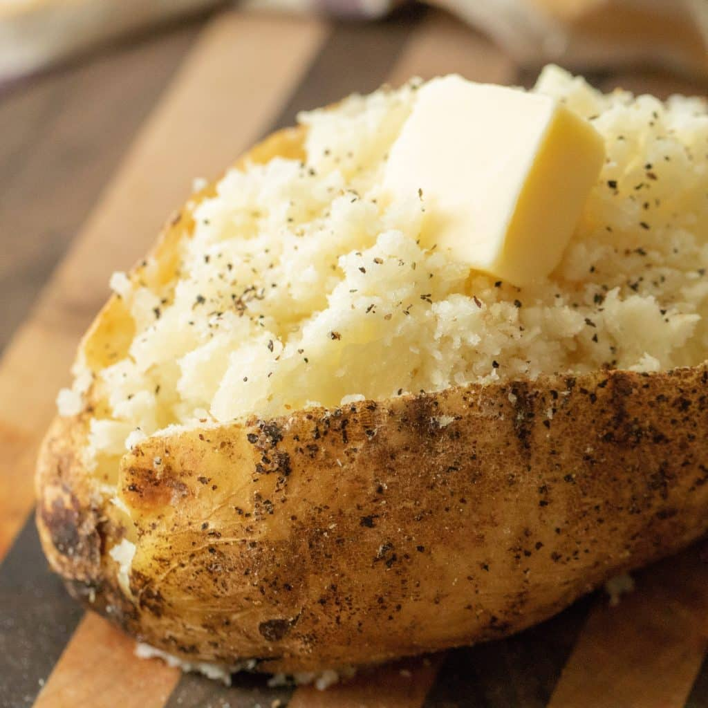 Grilled baked potato topped with pepper and a slice of butter.