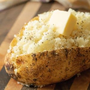 Sliced and fluffed grilled baked potato topped with salt, pepper, and a pad of butter.