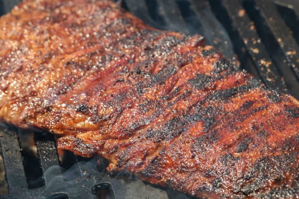 Seasoned skirt steak on the grill.