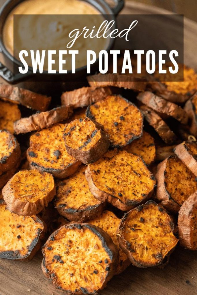grilled sweet potatoes on a wood cutting board with dipping sauce on the side in a cast iron bowl.