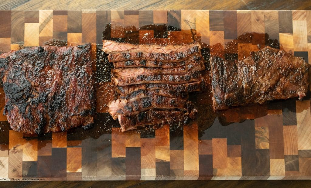 Cut skirt steak on a wooden cutting board.