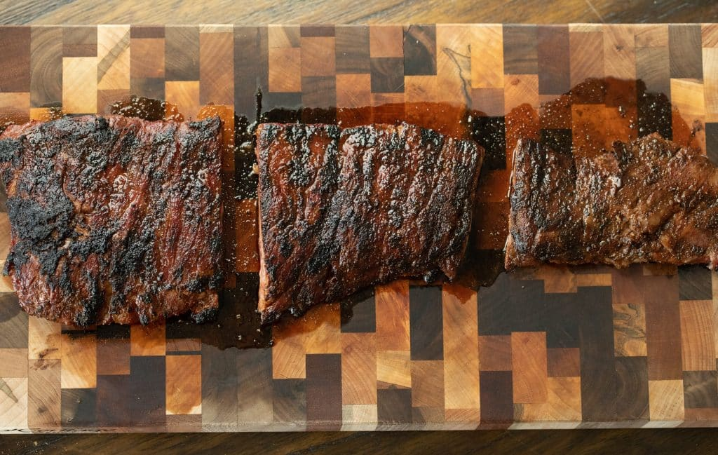 Skirt steak cut into three sections on a wooden cutting board.