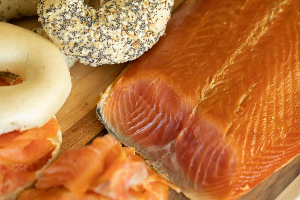 Cross section of smoked salmon filet with bagels and smoked salmon slices.