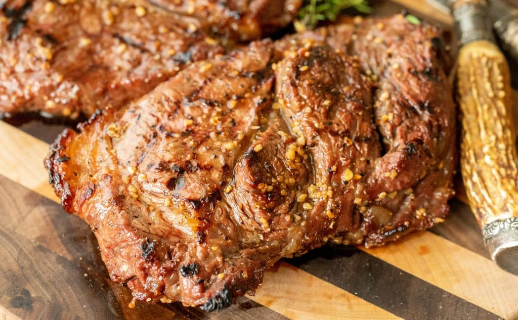 Grilled and marinated steak on a wooden cutting board