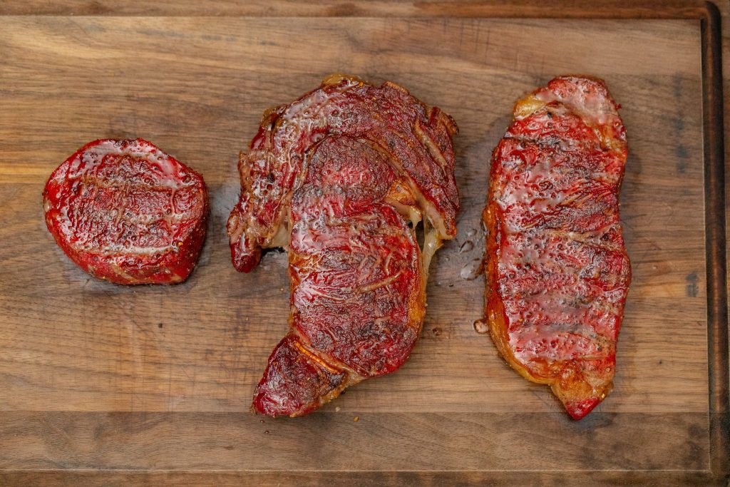 Three smoked steaks next to each other on the wood cutting board.
