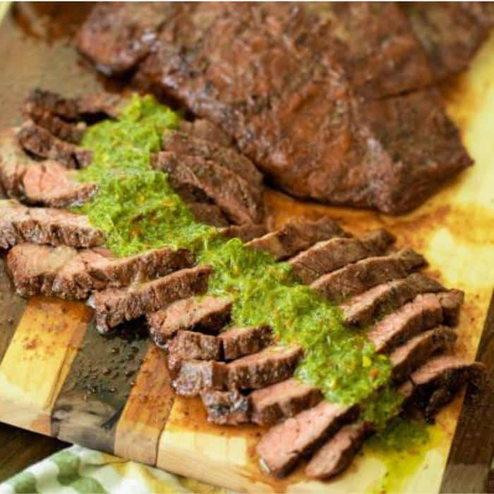 sliced grilled flap steak covered in chimichurri on a wooden cutting board