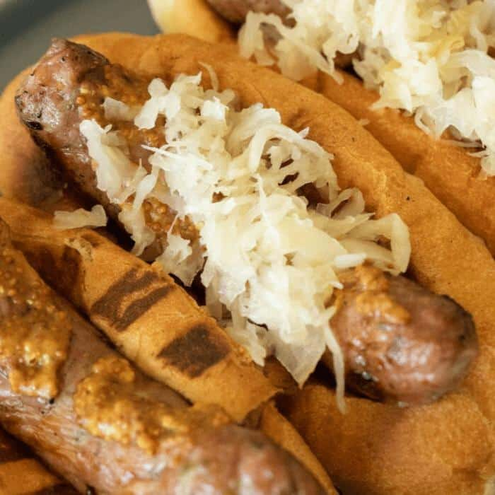 Two grilled bratwursts covered in mustard and sauerkraut