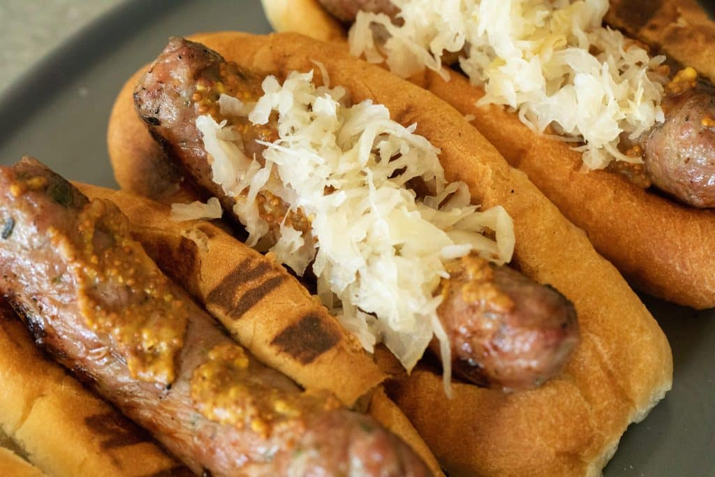 Grilled bratwurst in a bun with mustard and sauerkraut, overhead view displayed on a gray plate.