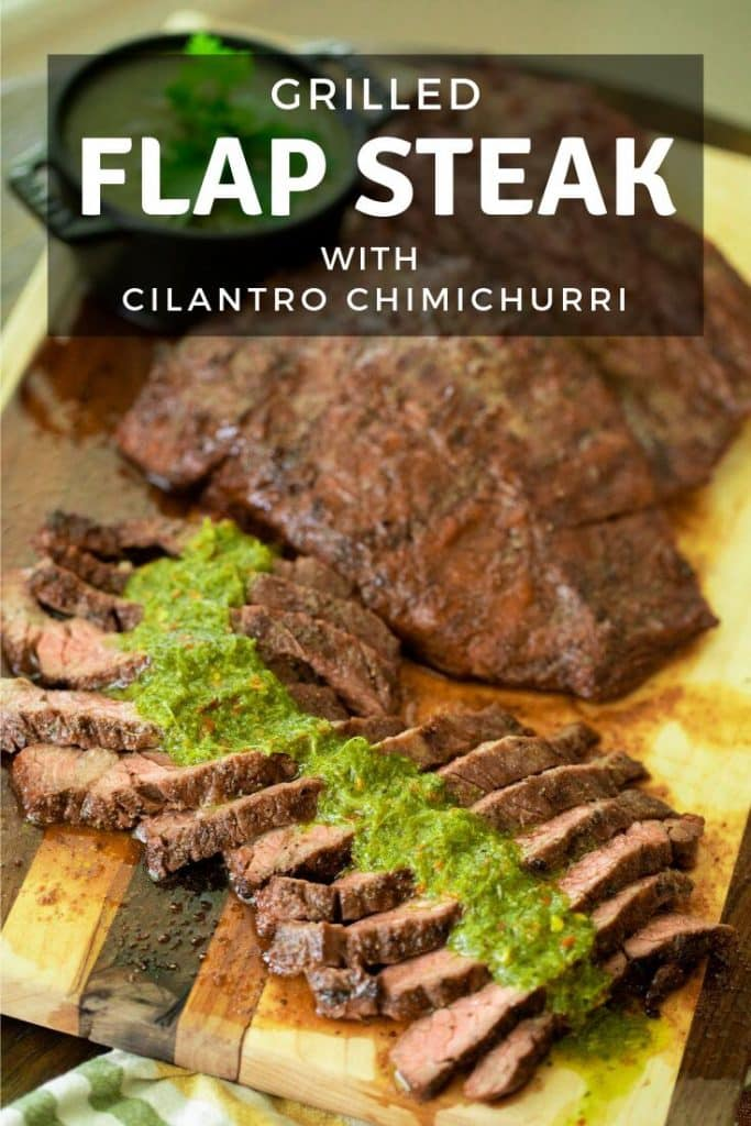 sliced flap steak topped with chimichurri sauce on a wood cutting board.