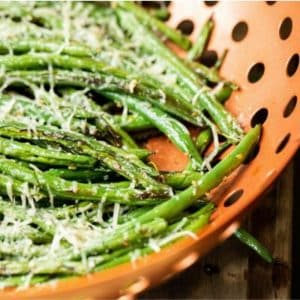Parmesan covered grilled green beans in a copper vegetable grilling wok.