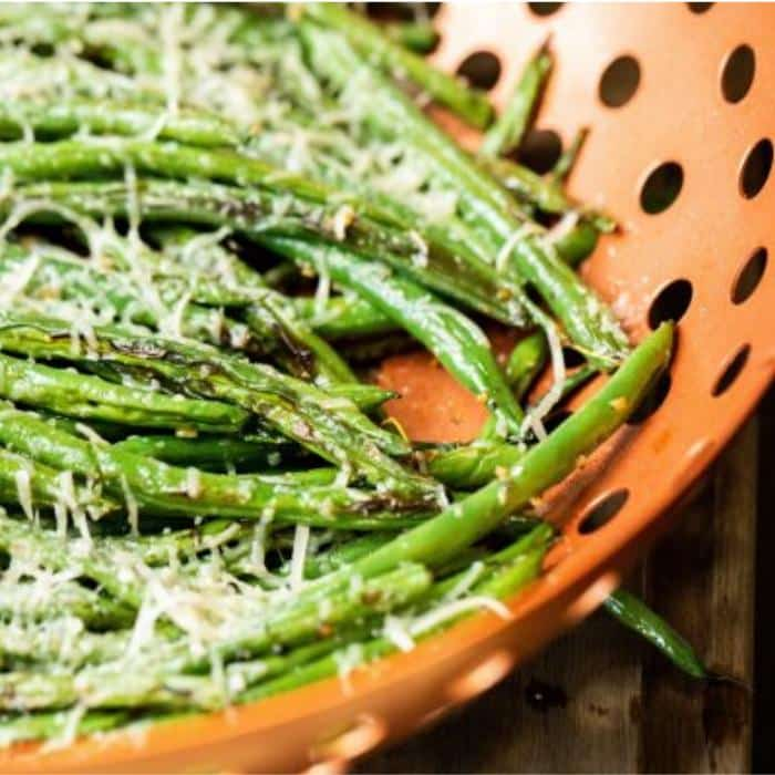 grilled green beans in a vegetable basket covered in melted, shredded Parmesan cheese