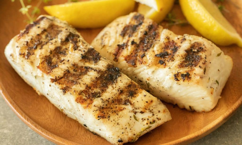 two grilled halibut fillets on a wooden plate with a side of sliced lemons.