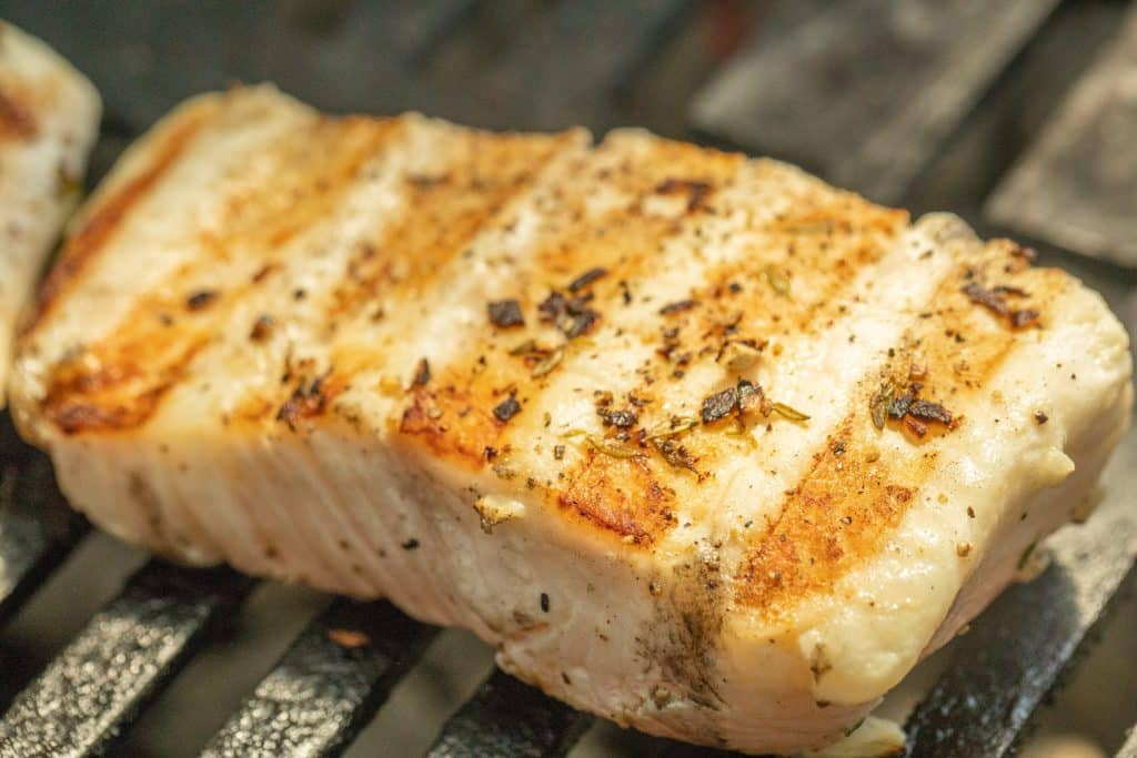 seasoned halibut fillet with grill marks on the grill.