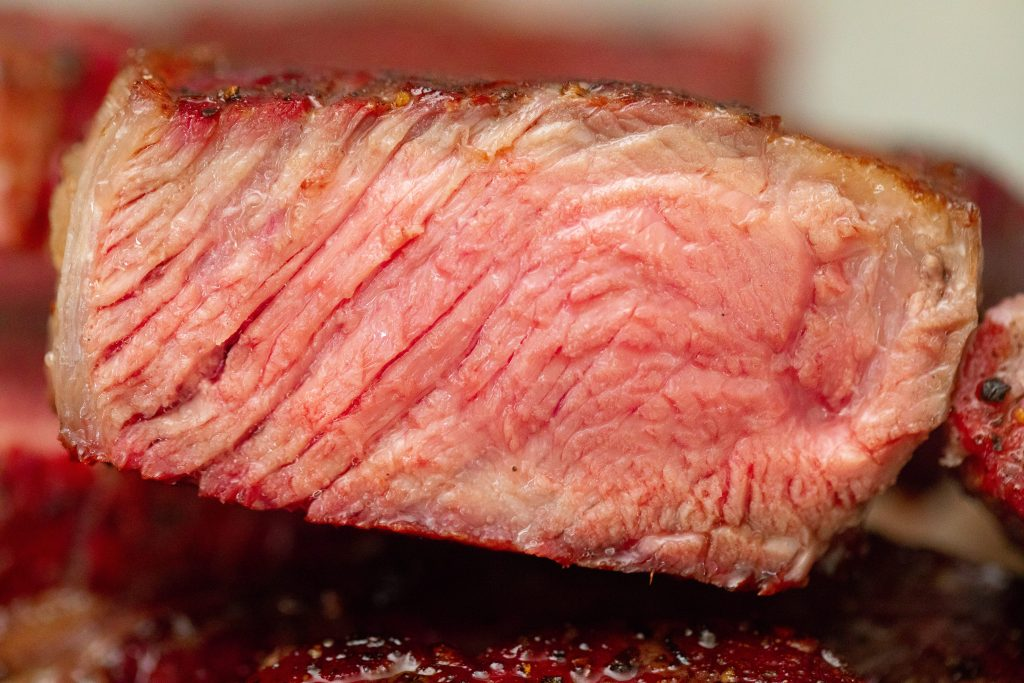 steak cooked to medium temperature, sliced open to show the inside of the steak.