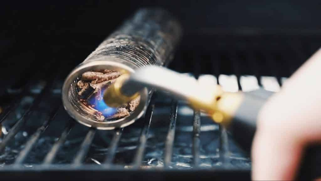 lighting a pellet smoke tube in a grill.