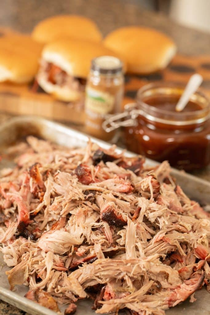 Smoked pork shredded in a metal pan, with a glass jar full of Pumpkin Pie sauce in the background.