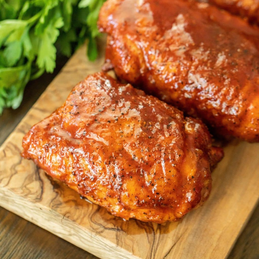 grilled chicken thighs covered in sauce and resting on a wooden cutting board