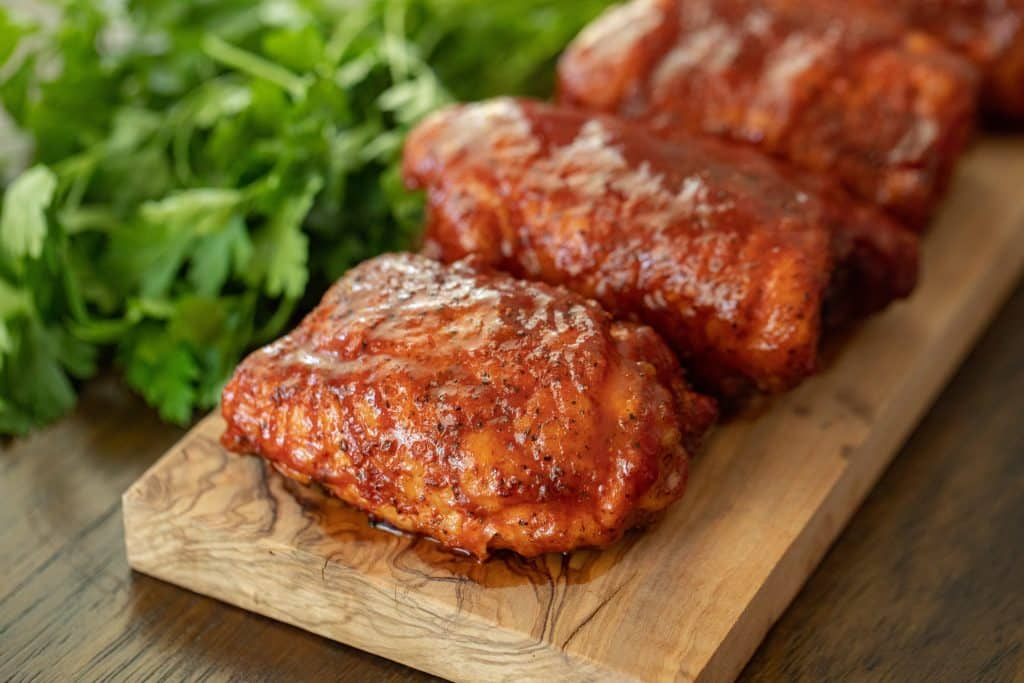smoked chicken thighs on a wooden board with green herbs behind.