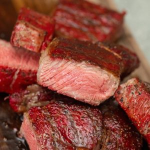 Slices of smoked steak cooked to medium rare in a pile.