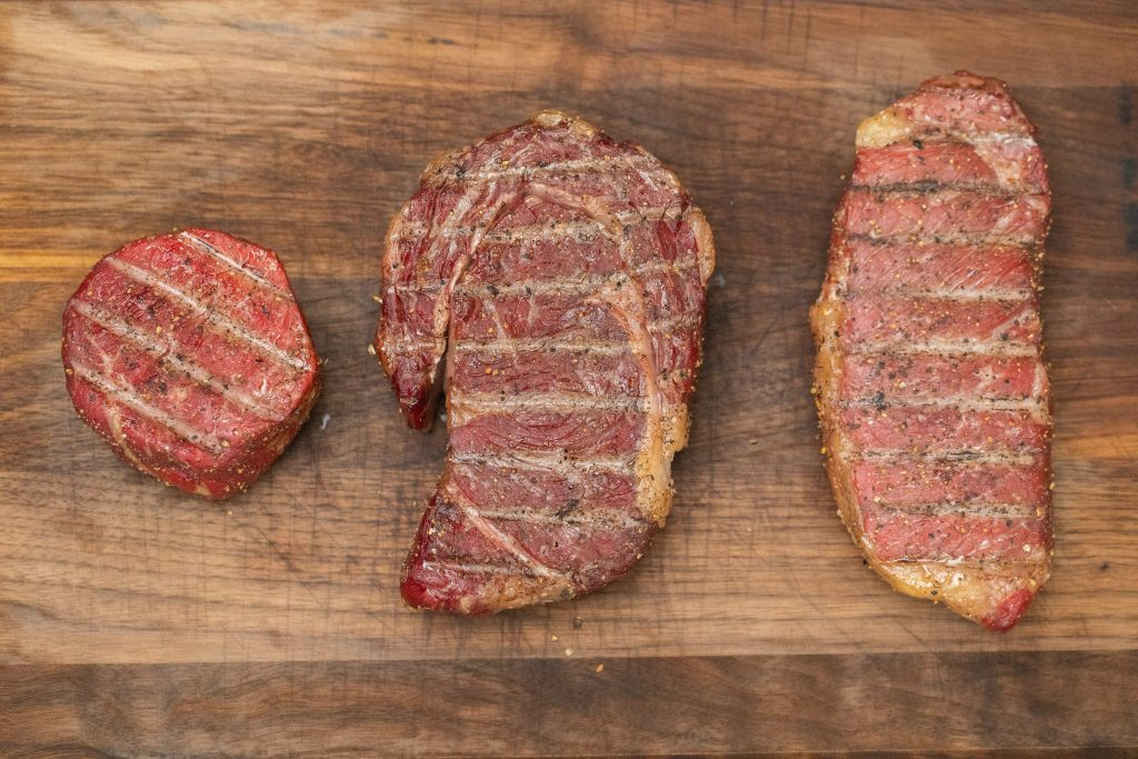Three different cuts of steak grilled and placed on a wooden cutting board.