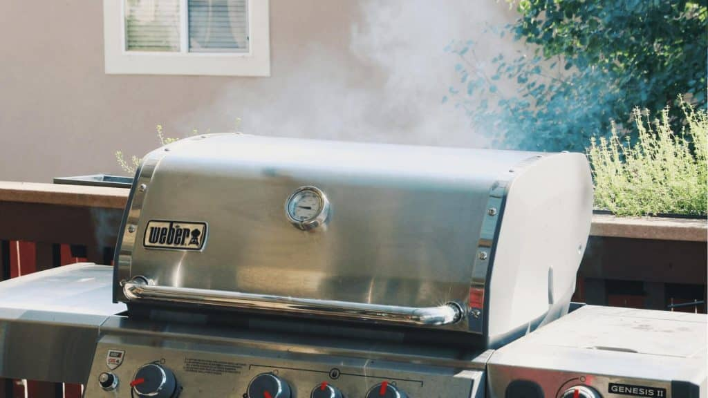 gas grill with smoke rising from the lid.