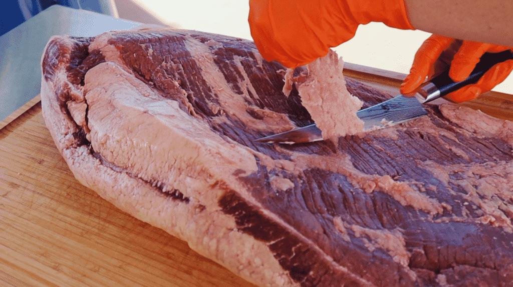 Close up shot of a brisket getting the fat trimmed off.