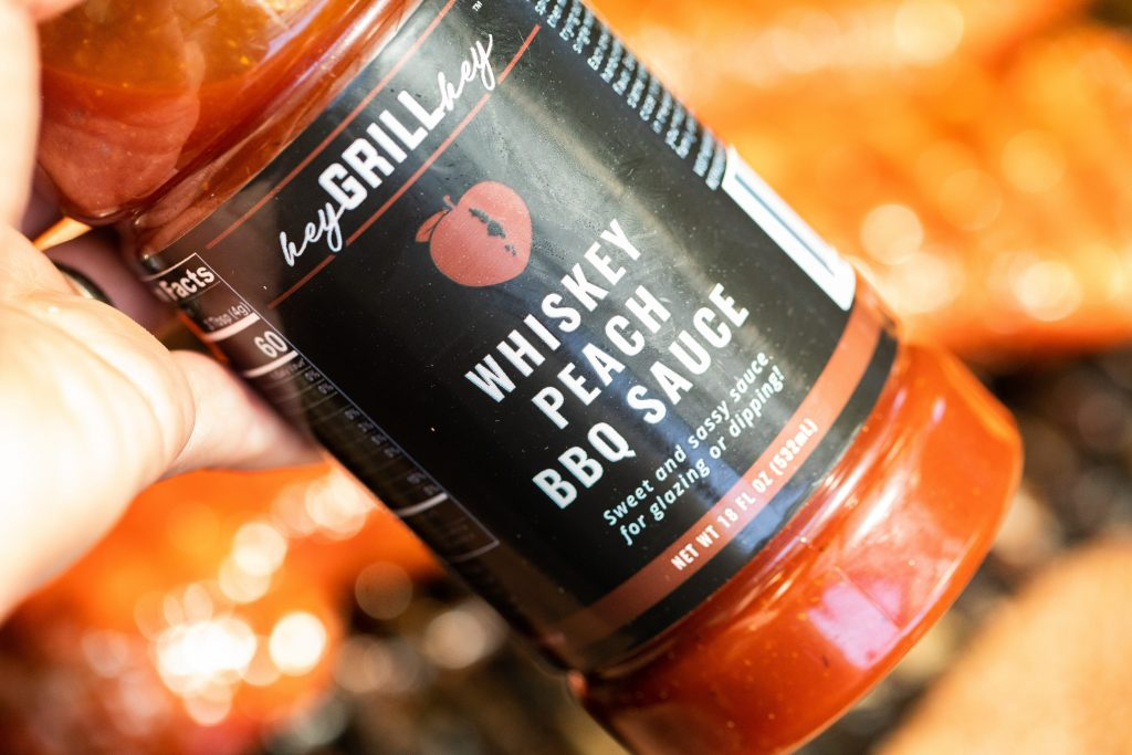 A bottle of Whiskey Peach BBQ sauce being held over smoked pork tenderloins.