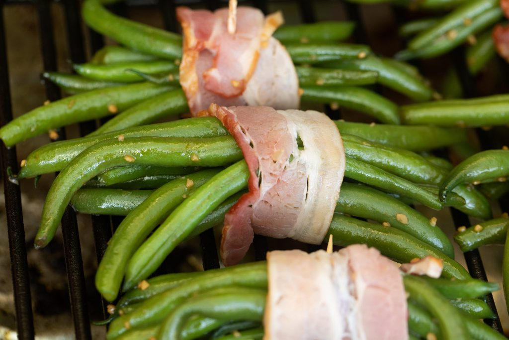 bacon wrapped green bean bundles on a grill