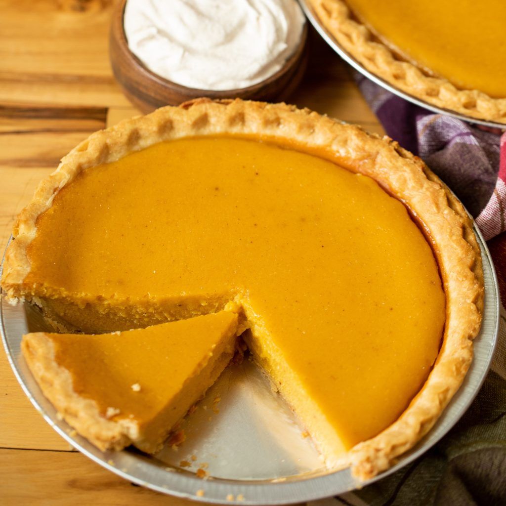 Sliced pumpkin pie in a pie tin next to another whole pie and a small bowl of whipped cream.