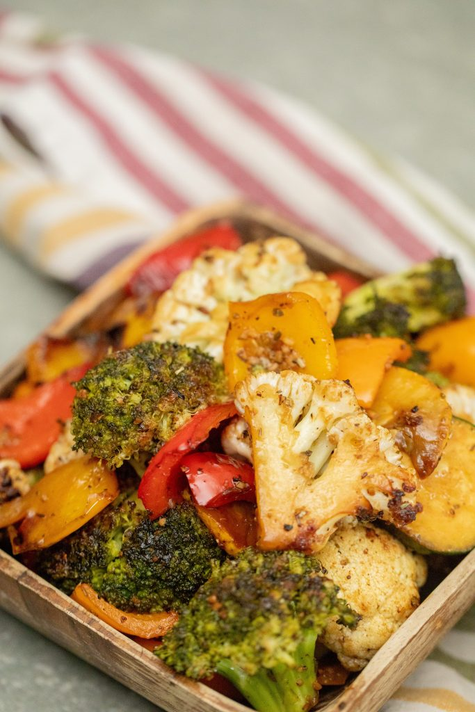 grilled vegetables in a wooden bowl on a striped towel.