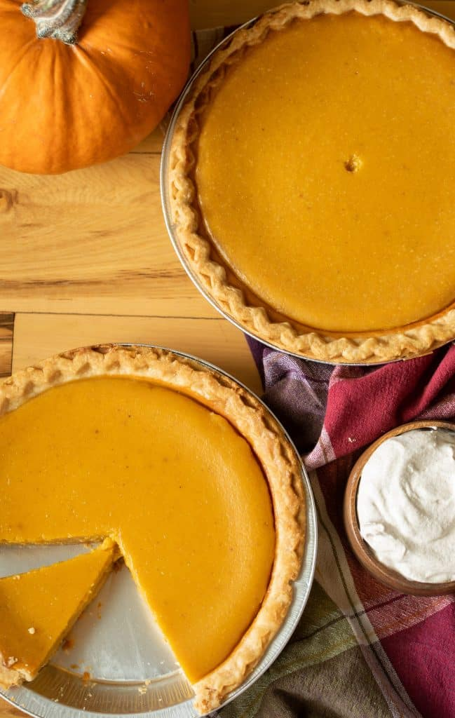 2 pumpkin pies on a wooden surface with a bowl of whipped cream and a small pumpkin.