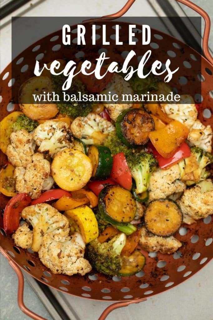 Seasoned grilled vegetables in a copper colored grill basket.