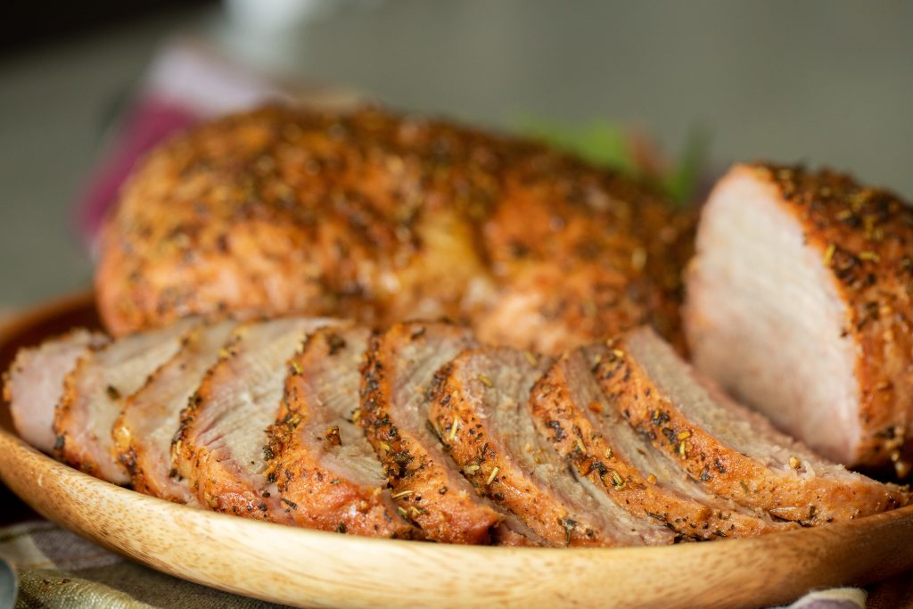 sliced smoked pork sirloin on a wooden plate.