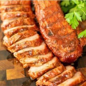 Sliced smoked pork tenderloin next to a whole smoked pork tenderloin on a wooden cutting board.