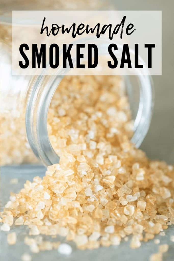 granules of smoked salt on a grey table pouring out of a glass jar.
