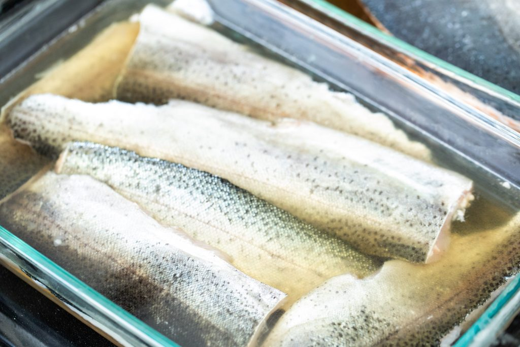 6 trout filets in a glass dish in a brining liquid.