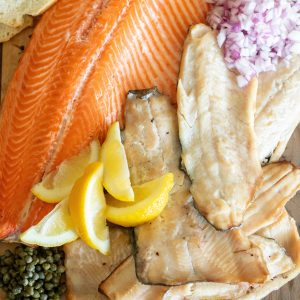 Whole fillets of smoked trout on a wooden board surrounded by sliced baguettes, lemon slices, and chopped onions.