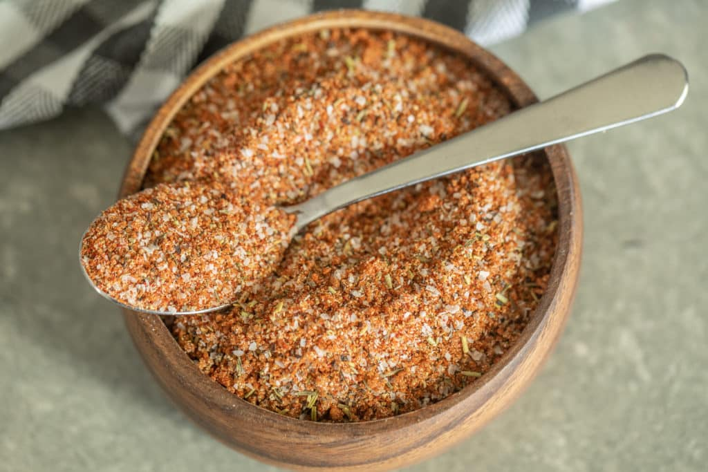 Spoonful of smoked turkey rub over a wooden bowl of smoked turkey rub.