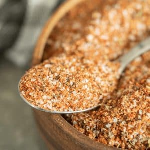 Spoonful of turkey rub resting on the edge of a wooden bowl full of the same rub.