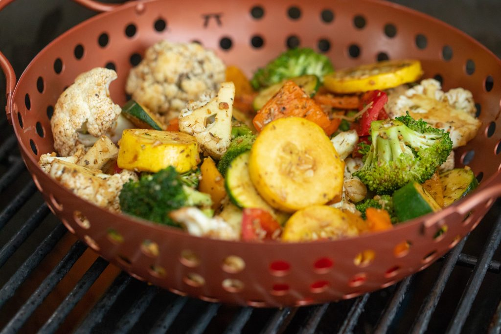 A maroon grill basket bowl with seasoned vegetables in a grill.