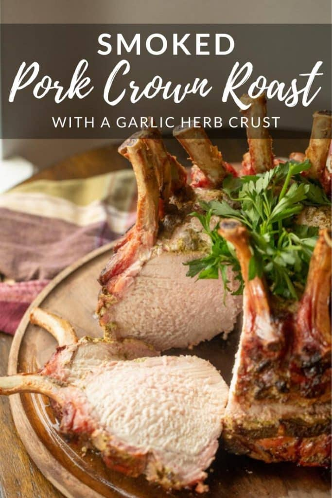 Smoked Pork Crown Roast on a wooden cutting board with two slices cut out and resting next to the roast.