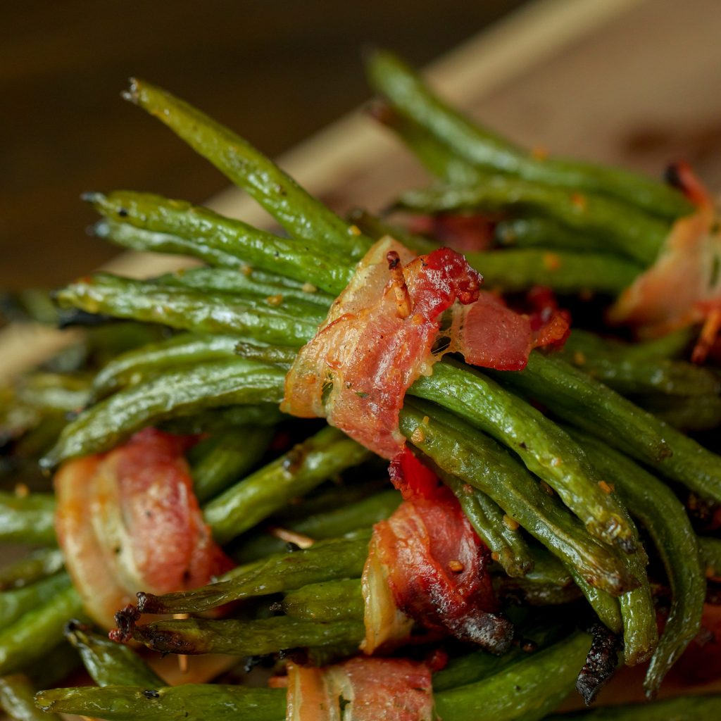 Bacon wrapped green bean bundles stacked on a metal baking dish.