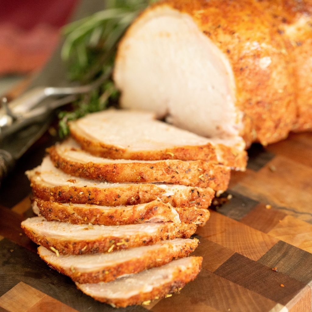 Smoked and sliced cider brined turkey breast lined up on a wooden cutting board.