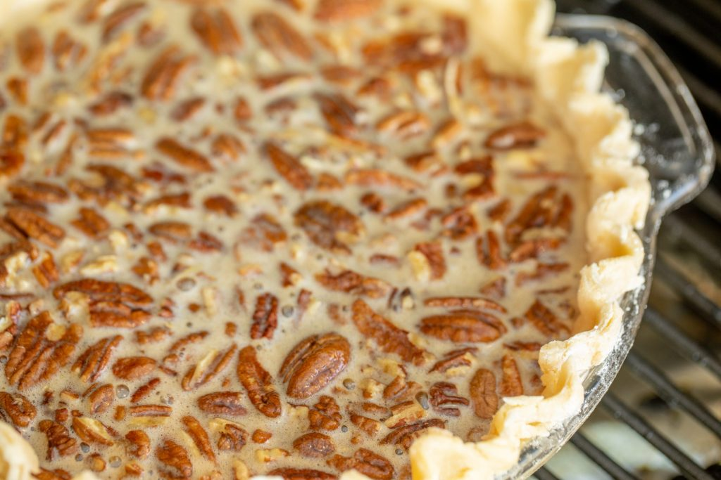 close up of a whole smoked pecan pie on the grill grates of a smoker.
